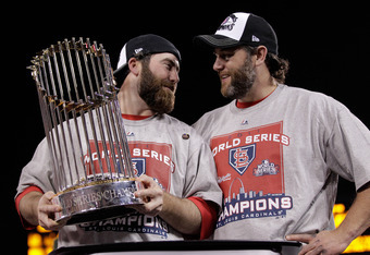 ST LOUIS, MO - OCTOBER 28:  (L-R) Jason Motte #30 and Lance Berkman #12 of the St. Louis Cardinals celebrate with the World Series trophy after defeating the Texas Rangers 6-2 in Game Seven of the MLB World Series at Busch Stadium on October 28, 2011 in S