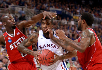 ST. LOUIS, MO - MARCH 23:  Thomas Robinson #0 of the Kansas Jayhawks draws contact as he drives in the first half against DeShawn Painter #0 of and Richard Howell #1 of the North Carolina State Wolfpack during the 2012 NCAA Men's Basketball Midwest Region