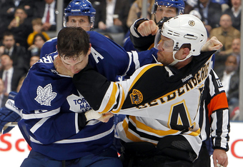 TORONTO, CANADA - MARCH 6: Colby Armstrong #9 of the Toronto Maple Leafs gets punched by Dennis Seidenberg #44 of the Boston Bruins during NHL action at the Air Canada Centre March 6, 2012 in Toronto, Ontario, Canada. (Photo by Abelimages/Getty Images)