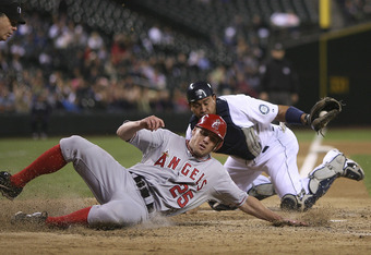 SEATTLE - SEPTEMBER 01:  Peter Bourjos #25 of the Los Angeles Angels of Anaheim is put out by catcher Miguel Olivo #30 of the Seattle Mariners while trying to score on a fielders choice by Torii Hunter at Safeco Field on September 1, 2011 in Seattle, Wash
