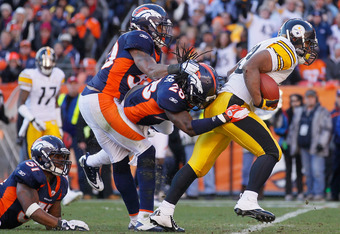 DENVER, CO - JANUARY 08:  Running back Isaac Redman #33 of the Pittsburgh Steelers is tackled from behind by Quinton Carter #28 of the Denver Broncos during the Wild Card Playoffs at Sports Authority Field at Mile High on January 8, 2012 in Denver, Colora