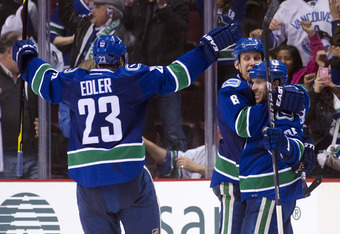 VANCOUVER, CANADA - MARCH 31: Andrew Ebbett #25 of the Vancouver Canucks is congratulated by Sami Salo #6 and Alexander Edler #23 after scoring the game winning goal against the Calgary Flames in overtime to win 3-2 during NHL action on March 31, 2012 at