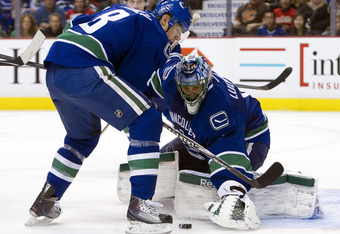VANCOUVER, CANADA - MARCH 31: Chris Tanev #8 of the Vancouver Canucks tries to help goalie Roberto Luongo #1 cover up the puck after making a save against the Calgary Flames during the third period in NHL action on March 31, 2012 at Rogers Arena in Vancou