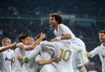 MADRID, SPAIN - NOVEMBER 26:  Marcelo (C) of Real Madrid celebrates with teammates after Angel di Maria (#7) scored his team's second goal during the La Liga match between Real Madrid and Atletico Madrid at Estadio Santiago Bernabeu on November 26, 2011 i