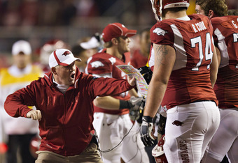 FAYETTEVILLE, AR - NOVEMBER 12:   Head Coach Bobby Petrino of the Arkansas Razorbacks shows his offensive lineman something during a game against the Tennessee Volunteers at Donald W. Reynolds Stadium Stadium on November 12, 2011 in Fayetteville, Arkansas