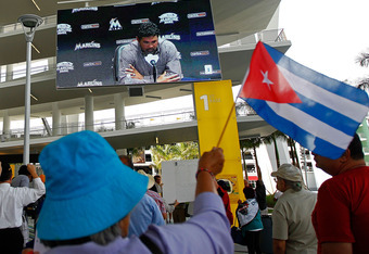 MIAMI, FL - APRIL 10:  Protesters rally outside as Miami Marlins Manager Ozzie Guillen seen on a screen speaks during a press conference about comments made about Fidel Castro at Marlins Park on April 10, 2012 in Miami, Florida. The Marlins suspended Guil