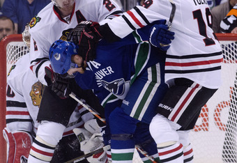 VANCOUVER, CANADA - APRIL 26: Duncan Keith #2 and Jonathan Toews #19 of the Chicago Blackhawks  ruff up Daniel Sedin #22 of the Vancouver Canucks in front of the goalie Corey Crawford #50 of the Chicago Blackhawks during the first period in Game Seven of