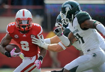 LINCOLN, NE - OCTOBER 29: Running back Aaron Green #2 of the Nebraska Cornhuskers runs through the Michigan State Spartans defense during their game against the Michigan State Spartans defense at Memorial Stadium October 29, 2011 in Lincoln, Nebraska. Neb