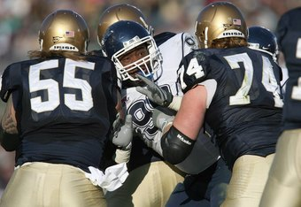 SOUTH BEND, IN - NOVEMBER 21: Kendall Reyes #99 of the Univeristy of Connecticut Huskies is tackled by Eric Olsen #55 andSam Young #74 of the Notre Dame Fighting Irish at Notre Dame Stadium on November 21, 2009 in South Bend, Indiana. (Photo by Jonathan D