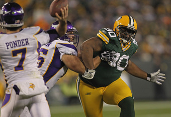 GREEN BAY, WI - NOVEMBER 14:  B.J. Raji #90 of the Green Bay Packers rushes against John Sullivan #65 of the Minnesota Vikings as Christian Ponder #7 throws a pass at Lambeau Field on November 14, 2011 in Green Bay, Wisconsin. The Packers defeated the Vik