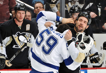 PITTSBURGH, PA - FEBRUARY 25: Deryk Engelland #5 of the Pittsburgh Penguins wrestles with Mike Angelidis #59 of the Tampa Bay Lightning on February 25, 2012 at CONSOL Energy Center in Pittsburgh, Pennsylvania. (Photo by Jamie Sabau/Getty Images)