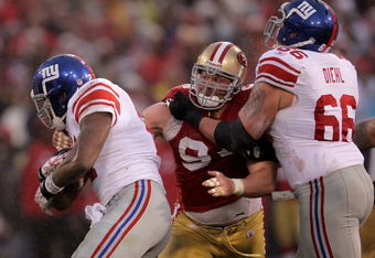 SAN FRANCISCO, CA - JANUARY 22:  Justin Smith #94 (C) of the San Francisco 49ers attempts to tackle Brandon Jacobs #27 (L) of the New York Giants as he is blocked by David Diehl #66 (R) during the NFC Championship Game at Candlestick Park on January 22, 2