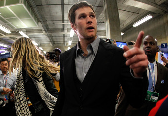 INDIANAPOLIS, IN - FEBRUARY 05:  Tom Brady #12 (R) of the New England Patriots chats with his wife Gisele Bundchen leave the press conference area after the Patriots lost 21-17 against the New York Giants during Super Bowl XLVI at Lucas Oil Stadium on Feb