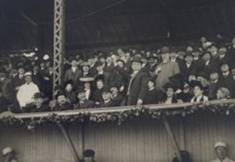 Here Honey Fitz (standing) is throwing out the first ball at Fenway's predecessor, the Huntington Avenue Grounds.