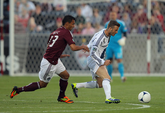 COMMERCE CITY, CO - APRIL 21:  David Beckham #23 of the Los Angeles Galaxy controls the ball against Kamani Hill #13 of the Colorado Rapids at Dick's Sporting Goods Park on April 21, 2012 in Commerce City, Colorado.  (Photo by Doug Pensinger/Getty Images)