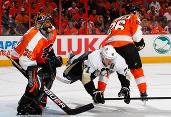 PHILADELPHIA, PA - APRIL 22:  Evgeni Malkin #71 of the Pittsburgh Penguins is sent flying by the stick of Erik Gustaffson #26 of the Philadelphia Flyers as Flyers goalie Ilya Bryzgalov #30 watches the puck in the first period of Game Six of the Eastern Co