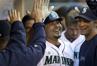 SEATTLE, WA - APRIL 14: Jesus Montero #63 of the Seattle Mariners is congratulated by teammates in the dugout after hitting a home run against the Oakland Athletics during a game at Safeco Field on April 14, 2012 in Seattle, Washington. (Photo by Stephen