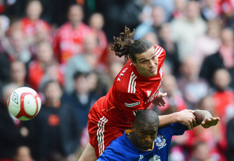 LONDON, ENGLAND - APRIL 14:  Andy Carroll of Liverpool outjumps Sylvain Distin of Everton during the FA Cup with Budweiser Semi Final match between Liverpool and Everton at Wembley Stadium on April 14, 2012 in London, England.  (Photo by Mike Hewitt/Getty