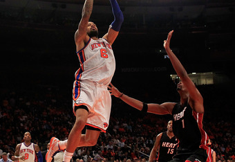 NEW YORK, NY - APRIL 15: Tyson Chandler #6 of the New York Knicks lays the ball up past Chris Bosh #1 of the Miami Heat at Madison Square Garden on April 15, 2012 in New York City. NOTE TO USER: User expressly acknowledges and agrees that, by downloading