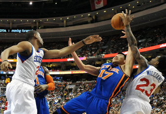 PHILADELPHIA, PA - MARCH 21: Jeremy Lin #17 of the New York Knicks battles for a rebound with Thaddeus Young #21 and Lou Williams #23 of the Philadelphia 76ers at the Wells Fargo Center on March 21, 2012 in Philadelphia, Pennsylvania. The Knicks won 82-79