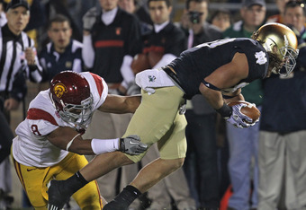 SOUTH BEND, IN - OCTOBER 22: Nick Perry #8 of the University of Southern California Trojans brings down Tyler Eifert #80 of the Notre Dame Fighting Irish at Notre Dame Stadium on October 22, 2011 in South Bend, Indiana. (Photo by Jonathan Daniel/Getty Ima