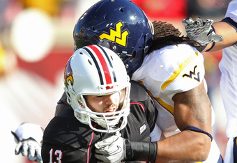LOUISVILLE, KY - NOVEMBER 20:  Justin Burke #13 of the Louisville Cardinals is sacked by Bruce Irvin #11 of the West Virginia Mountaineers during the game at Papa John's Cardinal Stadium on November 20, 2010 in Louisville, Kentucky.  (Photo by Andy Lyons/