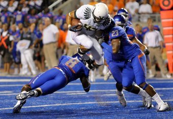 BOISE, ID - SEPTEMBER 3: Tight end David Paulson #42 of the Oregon Ducks leaps over George Iloka #8 of the Boise State Broncos as he is hit by safety Jeron Johnson #23 of the Boise State Broncos in the third quarter of the game on September 3, 2009 at Bro