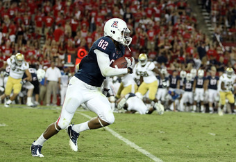TUCSON, AZ - OCTOBER 20:  Wide receiver Juron Criner #82 of the Arizona Wildcats runs with the football after a reception against the UCLA Bruins during the college football game at Arizona Stadium on October 20, 2011 in Tucson, Arizona.  (Photo by Christ