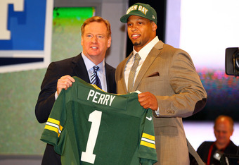 NEW YORK, NY - APRIL 26:  Nick Perry (R) from USC holds up a jersey as he stands on stage with NFL Commissioner Roger Goodell after he was selected #28 overall by the Green Bay Packers in the first round of the 2012 NFL Draft at Radio City Music Hall on A