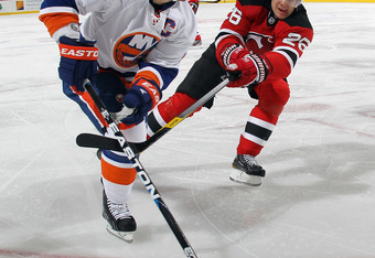 NEWARK, NJ - APRIL 03: Patrik Elias #26 of the New Jersey Devils checks Mark Streit #2 of the New York Islanders at the Prudential Center on April 3, 2012 in Newark, New Jersey.  (Photo by Bruce Bennett/Getty Images)