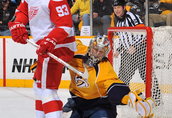 NASHVILLE, TN - APRIL 11: Goalie Pekka Rinne #35 of the Nashville Predators makes a save behind Johan Franzen #93 of the Detroit Red Wings in Game One of the Western Conference Quarterfinals during the 2012 NHL Stanley Cup Playoffs at the Bridgestone Aren