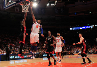 NEW YORK, NY - APRIL 15: J.R. Smith #8 of the New York Knicks lays the ball up past Dwyane Wade #3 of the Miami Heat at Madison Square Garden on April 15, 2012 in New York City. NOTE TO USER: User expressly acknowledges and agrees that, by downloading and