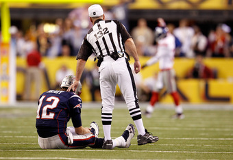 INDIANAPOLIS, IN - FEBRUARY 05:  Referee John Parry #132 stands over Tom Brady #12 of the New England Patriots as Brady sits on the turn against the New York Giants during Super Bowl XLVI at Lucas Oil Stadium on February 5, 2012 in Indianapolis, Indiana.