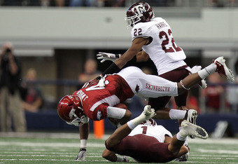 ARLINGTON, TX - OCTOBER 01:  Jarius Wright #4 of the Arkansas Razorbacks is tackled by Trent Hunter #1 and Dustin Harris #22 of the Texas A&M Aggies at Cowboys Stadium on October 1, 2011 in Arlington, Texas.  (Photo by Ronald Martinez/Getty Images)