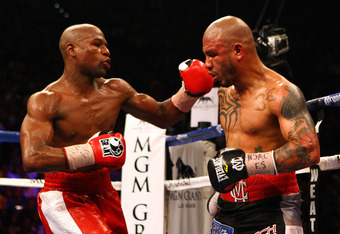 LAS VEGAS, NV - MAY 05:  (L-R) Floyd Mayweather Jr. throws a left to the face of Miguel Cotto during their WBA super welterweight title fight at the MGM Grand Garden Arena on May 5, 2012 in Las Vegas, Nevada.  (Photo by Al Bello/Getty Images)