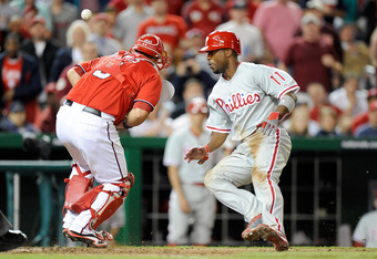 WASHINGTON, DC - MAY 06:  Jimmy Rollins #11 of the Philadelphia Phillies scores in the ninth inning as the ball gets away from Wilson Ramos #3 of the Washington Nationals at Nationals Park on May 6, 2012 in Washington, DC.  (Photo by Greg Fiume/Getty Imag