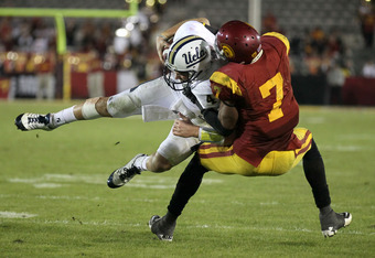 LOS ANGELES, CA - NOVEMBER 26: Quarterback Kevin Prince #4 of the UCLA Bruins is tackled by safety T.J McDonald #7 of the USC Trojans in the fourth quarter at the Los Angeles Memorial Coliseum on November 26, 2011 in Los Angeles, California.  USC won 50-0