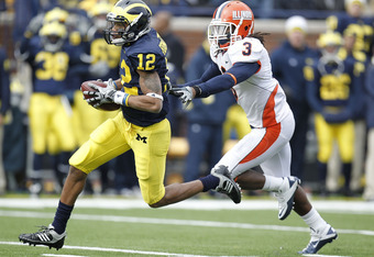 ANN ARBOR, MI - NOVEMBER 06:  Roy Roundtree #12 of the Michigan Wolverines gets past the tackle of Tavon Wilson #3 of the Illinios Fighting Illini after a second quarter reception at Michigan Stadium on November 6, 2010 in Ann Arbor, Michigan.  (Photo by