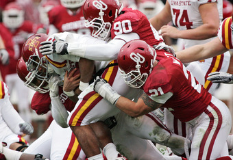 NORMAN, OK - NOVEMBER 26:  Quarterback Jared Barnett #16 of the Iowa State Cyclones is grabbed by the Oklahoma Sooner defense in the first half on November 26, 2011 at Gaylord Family-Oklahoma Memorial Stadium in Norman, Oklahoma. Oklahoma defeated Iowa St