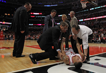 CHICAGO, IL - APRIL 28:  Derrick Rose #1 of the Chicago Bulls is lifted off of the court as coach Tom Thibodeau (L) watches after suffering a knee injury against the Philadelphia 76ers in Game One of the Eastern Conference Quarterfinals during the 2012 NB
