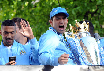MANCHESTER, ENGLAND - MAY 14:  Sergio Aguero of Manchester City celebrates with the Barclays Premier League trophy next to team-mate Gael Clichy in front of Manchester Town Hall during the victory parade around the streets of Manchester on May 14, 2012 in