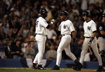 18 Oct 1998:  Outfielders Bernie Williams #51, Chili Davis #45 and infielder Derek Jeter #2 of the New York Yankees celebrate a home run during the 1998 World Series Game 2 against the San Diego Padres at the Yankee Stadium in the Bronx, New York. The Yan