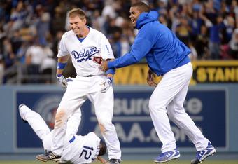 AJ Ellis, Justin Sellers (12) and Kenley Jansen celebrate the Dodgers' walk-off win.