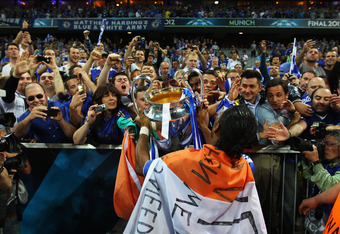 MUNICH, GERMANY - MAY 19:  Didier Drogba of Chelsea celebrates with the trophy in front of their fans after their victory in the UEFA Champions League Final between FC Bayern Muenchen and Chelsea at the Fussball Arena München on May 19, 2012 in Munich, Ge
