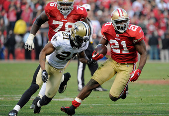 SAN FRANCISCO, CA - JANUARY 14:  Frank Gore #21 of the San Francisco 49ers carries the ball away from Patrick Robinson #21 of the New Orleans Saints during the NFC Divisional playoff game at Candlestick Park on January 14, 2012 in San Francisco, Californi