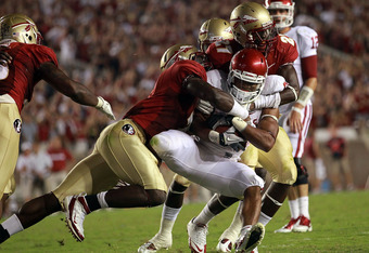 TALLAHASSEE, FL - SEPTEMBER 17:  Dominique Whaley #8 of the Oklahoma Sooners is tackled by Christian Jones #7 and Xavier Rhodes #27 of the Florida State Seminoles at Doak Campbell Stadium on September 17, 2011 in Tallahassee, Florida.  (Photo by Ronald Ma