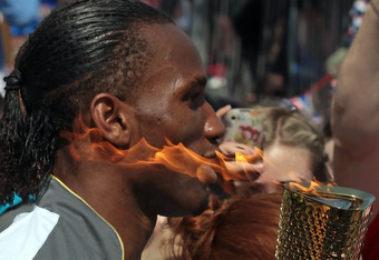 SWINDON, ENGLAND - MAY 23:  Footballer Didier Drogba carries the Olympic flame through Swindon on May 23, 2012 in Wiltshire, England. The Olympic Flame arrived in the UK last Friday and is now on day five of a 70-day relay involving 8,000 torchbearers cov
