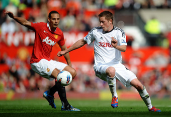 MANCHESTER, ENGLAND - MAY 06:  Gylfi Sigurdsson of Swansea City competes with Rio Ferdinand of Manchester United during the Barclays Premier League match between Manchester United and Swansea City at Old Trafford on 6 May 2012 in Manchester, England. (Pho
