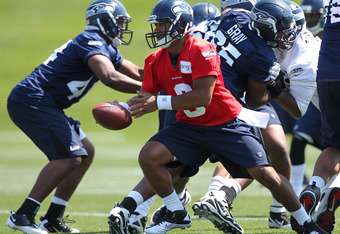 RENTON, WA - MAY 11:  Quarterback Russell Wilson #3 of the Seattle Seahawks looks to hand off during minicamp at the Virginia Mason Athletic Center on May 11, 2012 in Renton, Washington. (Photo by Otto Greule Jr/Getty Images)