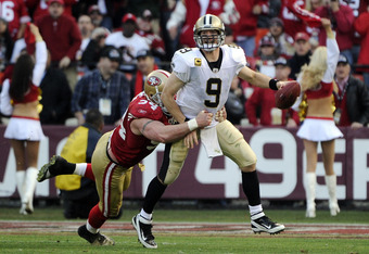 SAN FRANCISCO, CA - JANUARY 14:  Drew Brees #9 of the New Orleans Saints tries to escape the grasp of defensive tackle Justin Smith #94 of the San Francisco 49ers  during the Divisional Playoffs at Candlestick Park on January 14, 2012 in San Francisco, Ca
